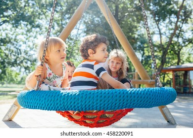 Kids in big swing at the playground. Children playing outdoors.