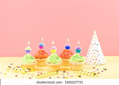 Kids birthday party accessories - colorful cupcakes with burning candles, party hat, streamers, confetti. Copy space