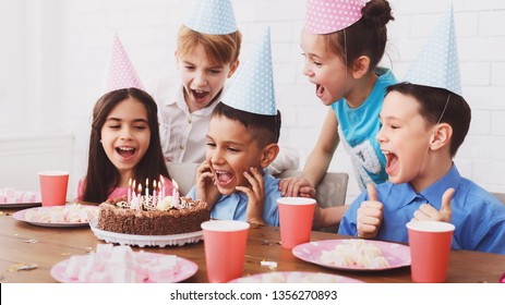 Kids Birthday Party Boy Blowing Out Candles On Cake Making Wish