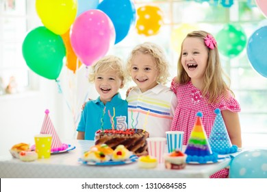 Kids birthday party. Child blowing out candles on colorful cake. Decorated home with rainbow flag banners, balloons. Farm animals theme celebration. Little boy celebrating birthday. Party food.