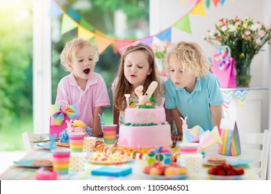 Kids birthday party. Children blow out candles on pink bunny cake. Pastel rainbow decoration and table setting for kids event, banner and flag. Girl and boy with birthday presents. Family celebration.