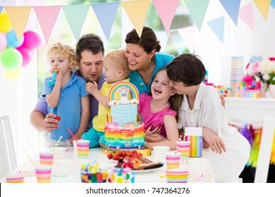 Kids birthday party with unicorn rainbow cake for little girl. Family celebrating child birthday. Parents and children blowing candles at baby cake. Balloons and colorful pastel banner decoration.