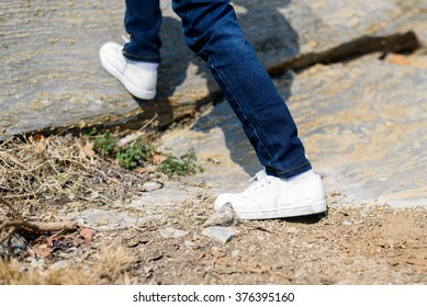 Kids in blue jean walking through the rough rocky land in the day time with strong sunlight.
