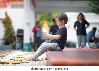 kids boy does not wants to going out of playland, insist to stay continually play game on line in mobile phone, family are keep waiting and shouting in back ground