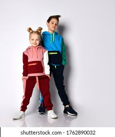 Kids, boy and girl, in colorful tracksuits and sneakers. They smiling, posing isolated on white studio background. Hands in pockets. Childhood, fashion, advertising and sport. Full length, copy space