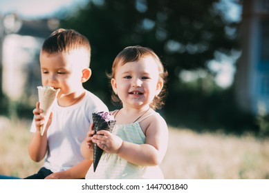 kids boy and girl eating ice cream in the evening on the bench is very cute