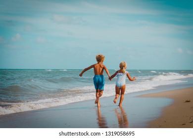 kids- boy and girl -running on tropical beach
