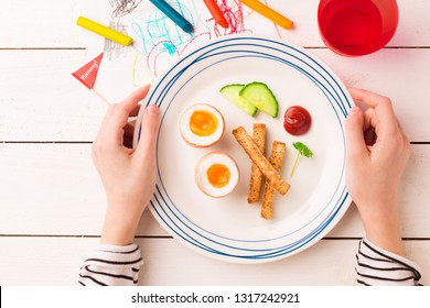 Kid's breakfast - eggs, toasts, cucumber and ketchup. Plate in child's hands on white wooden table. Captured from above (top view, flat lay).