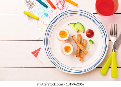 Kid's breakfast - eggs, toasts, cucumber and ketchup. Plate captured from above (top view, flat lay) on white wooden table. Layout with free copy (text) space.