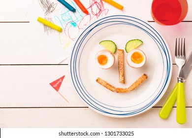 Kid's breakfast - funny face made of eggs, toasts and cucumber. Plate captured from above (top view, flat lay) on white wooden table. Layout with free copy (text) space.