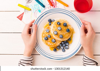 Kid's breakfast meal - pancakes, blueberries and maple syrup. Plate in child's hands on white wooden table. Captured from above (top view, flat lay).