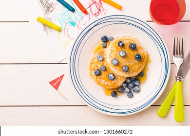 Kid's breakfast meal - pancakes, blueberries and maple syrup. Plate captured from above (top view, flat lay) on white wooden table. Layout with free copy (text) space.