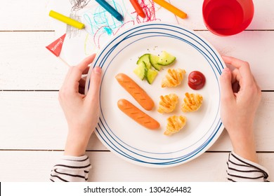 Kid's breakfast - weenies, mini croissants and cucumber salad. Plate in child's hands on white wooden table. Captured from above (top view, flat lay).