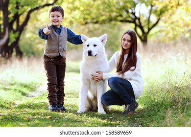 kids, brother and older sister plaing with their dog in the park, autumn