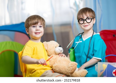 kids brothers play doctor with plush toy at home