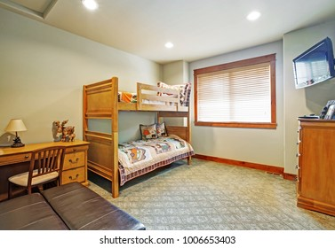 Kids' bunk room features bunk bed layered with bright car pattern bedding, wooden desk with drawers and flatscreen TV on the opposite side of the room. Northwest, USA