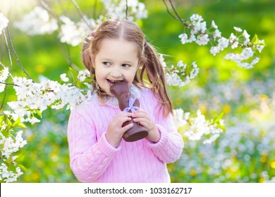 Kids with bunny ears on Easter egg hunt in blooming cherry blossom garden. Little girl eating chocolate rabbit. Spring flowers and eggs basket in fruit orchard. Children with Easter candy and sweets.