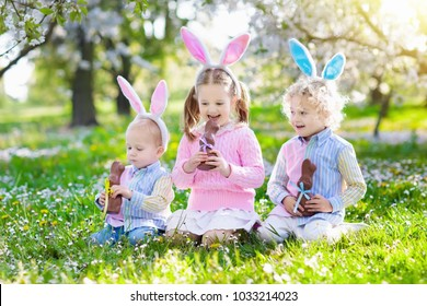 Kids with bunny ears on Easter egg hunt in blooming cherry blossom garden. Little boy and girl eat chocolate rabbit. Spring flowers and eggs basket in fruit orchard. Children with candy and sweets.