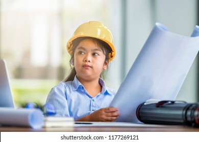 Kids, Business and Education concept - Cute girl dressed as an architect working on a blueprint and Little girl thinking about her future.