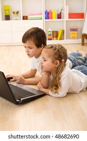 Kids busy and concentrated working on a laptop laying on the floor in their room