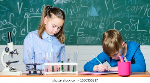 Kids busy study chemistry. School chemistry lesson. School laboratory. Girl and boy smart students conduct school experiment. Describe chemical reaction notepad. School education. Chemical analysis.