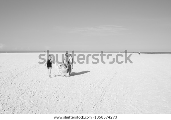 Kids carrying tent when walking to take a swim on the beach in Florida USA