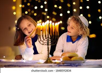 Kids celebrating Hanukkah. Jewish festival of lights. Children lighting candles on traditional menorah. Boy in kippah with dreidel and Sufganiyah doughnut. Israel holiday.