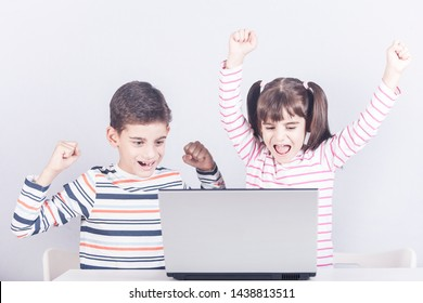 Kids celebrating with their hands in the air in front of a laptop computer