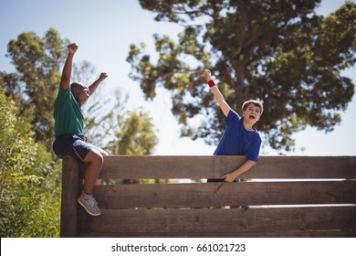 Kids cheering on wooden wall during obstacle course in boot camp