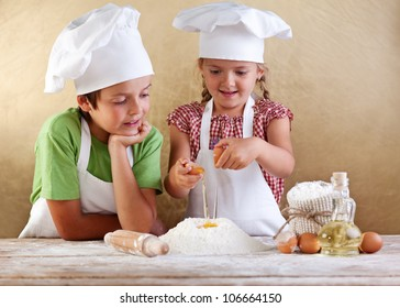 Kids with chef hats preparing a cake or pizza dough - breaking the eggs in the flour heap