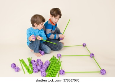 Kids, children building a fort and sharing construction pieces
