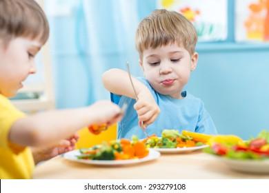 kids children eating vegetables in kindergarten or at home