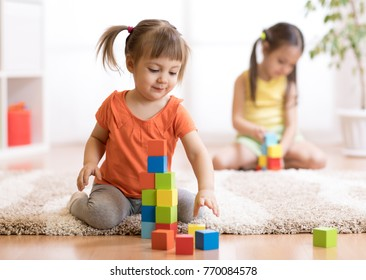 Kids children playing block toys in playroom at nursery