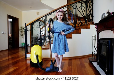 Kids cleaning the room - adorable kid girl using a vacuum cleaner