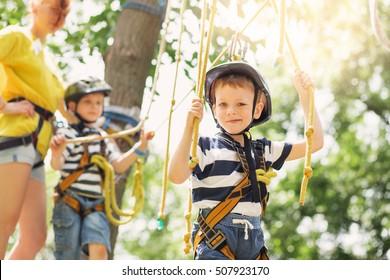 Kids climbing in adventure park in summer camp