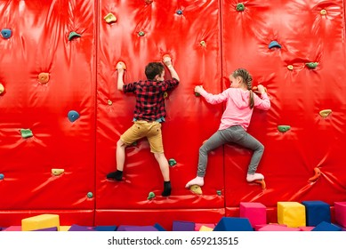 Kids climbing on a wall in attraction playground