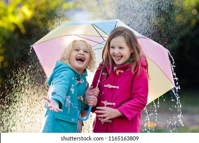 Kids with colorful umbrella playing in autumn shower rain. Little boy and girl in warm duffle coat play in a park by rainy weather. Fall outdoor fun for children. Kid catching rain drops.
