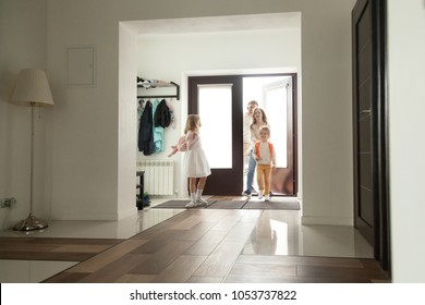 Kids coming back home with parents mom and dad, smiling cute children siblings with backpacks returning from school entering big modern hall, family of four happy to arrive at the house together
