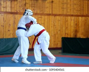 Kids compete in Jiu Jitsu. One boy beats the other in the head
