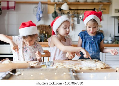 Kids cooking Christmas cookies in cozy kitchen. Sisters prepare holiday food for family together. Cute girls bake homemade festive biscuits. Lifestyle moment. Santa helpers. Children chef concept