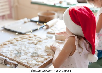 Kids cooking Christmas cookies in cozy home kitchen. Children prepare holiday food for family. Cute little girls bake homemade festive gingerbreads. Lifestyle moment. Santa helper.