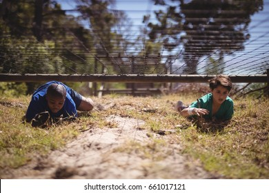 Kids crawling under the net during obstacle course in boot camp
