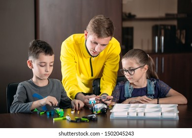 Kids creating robots with teacher. Early development, diy, innovation, modern technology concept