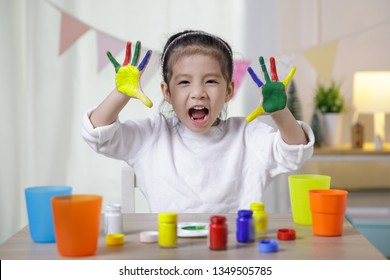 Kid's creativity, Child little asian girl hands painted in colorful paints in the class room at home, Educational concept for school