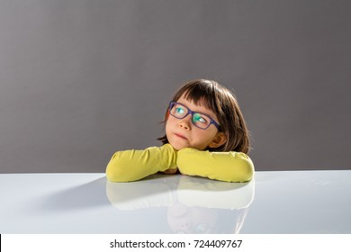 kid's critical thinking with serious little child leaning her head on a school table, looking away with imagination, reflection, doubt and gifted thoughts about future, copy space