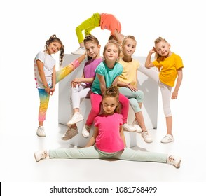 The kids dance school, ballet, hiphop, street, funky and modern dancers on white studio background. Girl is showing aerobic and dance element. Sublings day.