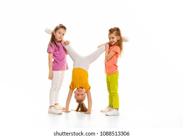 The kids dance school, ballet, hiphop, street, funky and modern dancers on white studio background. Girl is showing aerobic and dance element. Teen in hip hop style