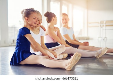 Kids dancing ballet sitting on floor and embracing while smiling together in the class.