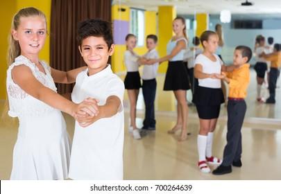 Kids are dancing tango in class.