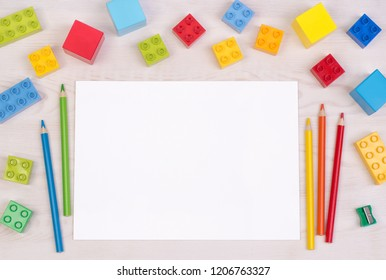 Kid's desk with colorful building blocks and pencils, top view with copy space